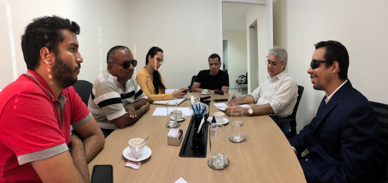 #PraCegoVer: O vereador Lucas Aribé está reunido com mais quatro pessoas, sendo uma mulher e todos estão sentados ao redor de uma mesa