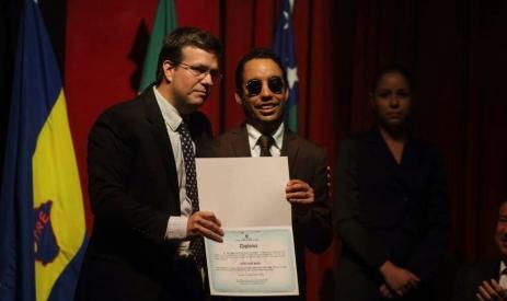 O vereador Lucas Aribé está recebendo seu diploma das mãos do promotor da 2ª Zona Eleitoral, Henrique Ribeiro Cardoso.