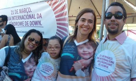 Vereador Lucas Aribé sorrindo em pé ao lado de uma criança que possui Síndrome de Down