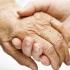 A imagem mostra uma mão de uma pessoa idosa sendo segurada pela mão de uma pessoa mais jovem