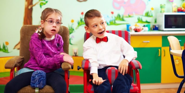 A imagem mostra duas crianças com deficiência posando para a foto