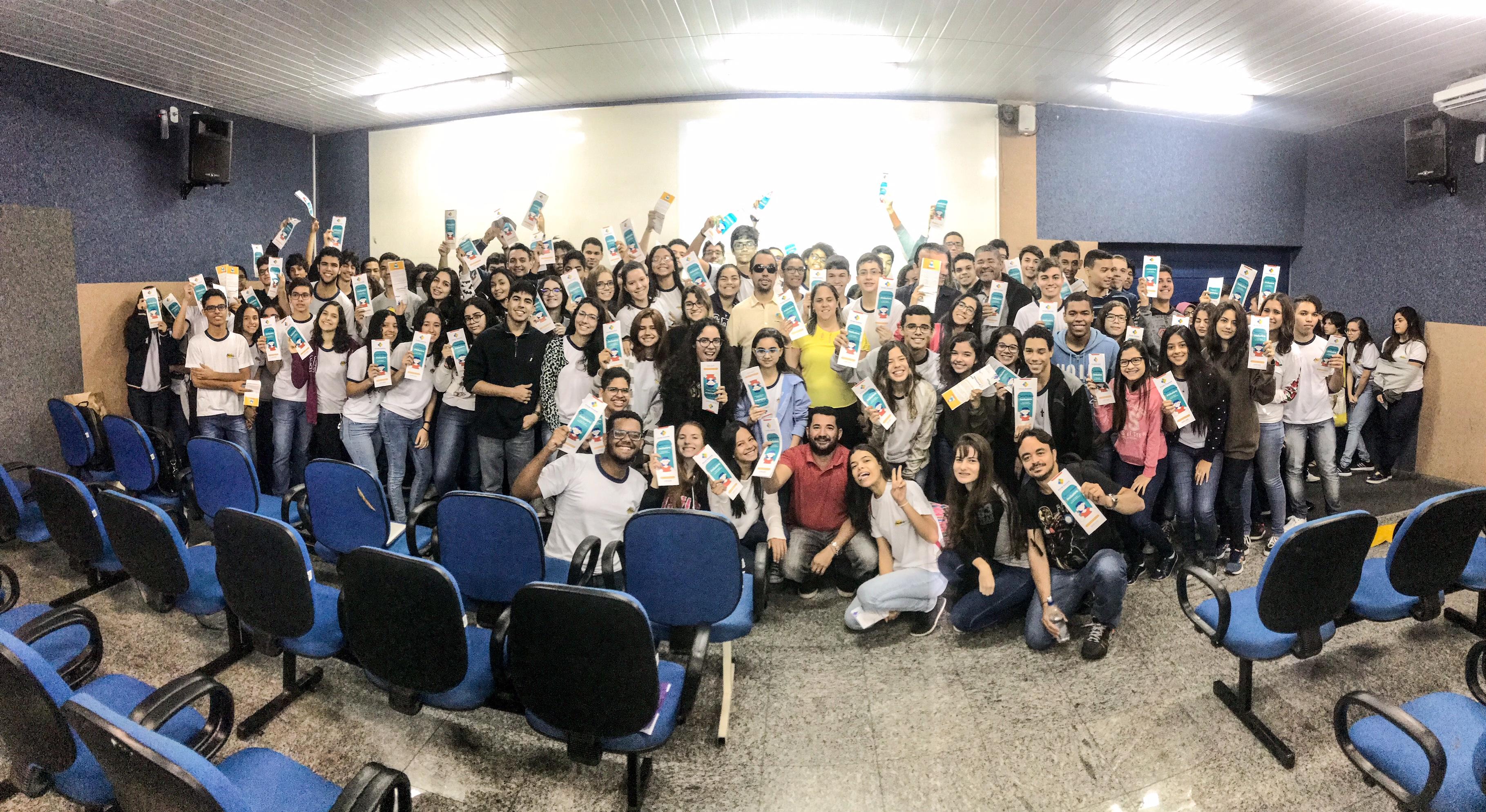 #PraCegoVer: Lucas entre alunos e professores. Todos exibem a cartilha com dicas de comunicação inclusiva