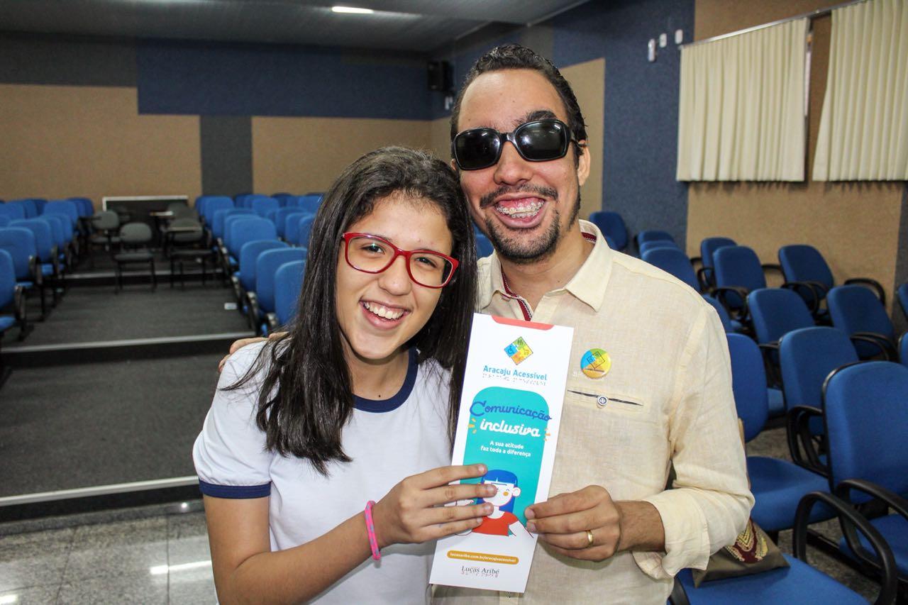 #PraCegoVer: Lucas entrega cartilha à estudante Mariana Laysa