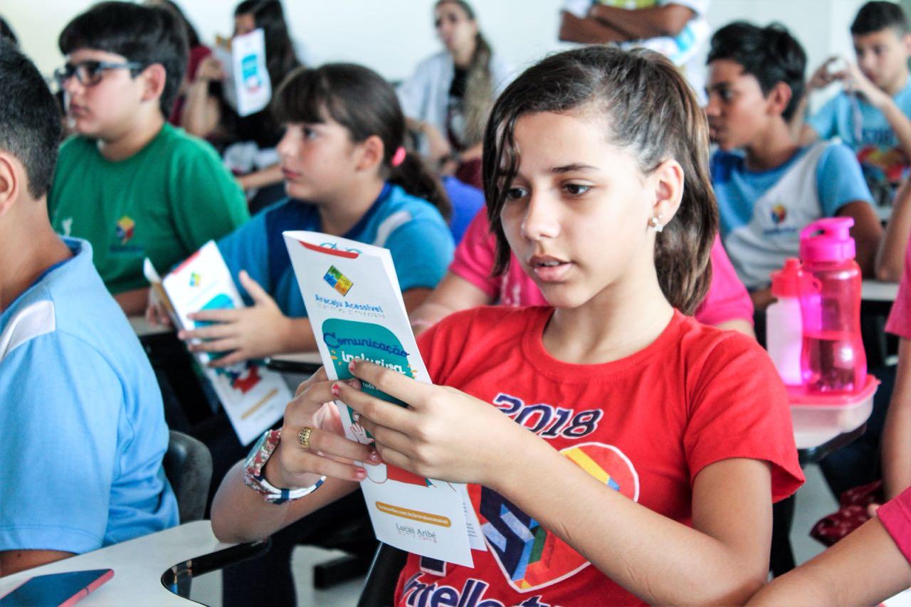 #PRaCegoVer: Garota lê atentamente as dicas da cartilha