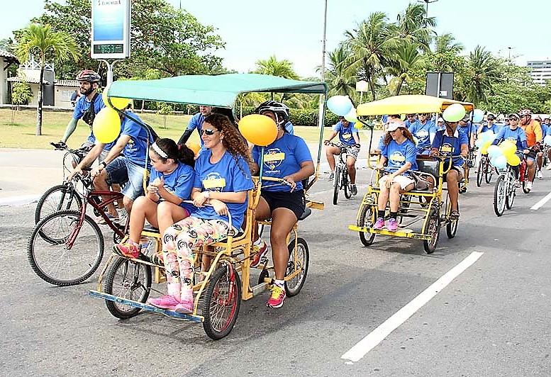 #PraCegoVer - Imagem de passeio ciclístico anterior, com pessoas pedalando em triciclos e quadriciclos