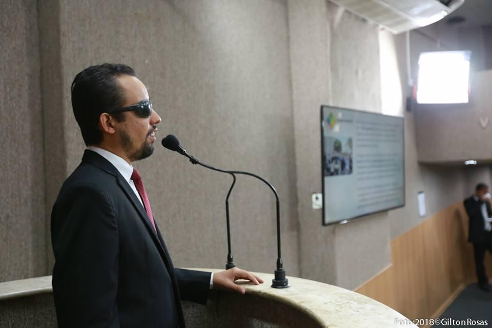 #PraCegoVer: A foto mostra o vereador Lucas Aribé falando no microfone da tribuna da Câmara e no telão do plenário mostra os slides da Semana Aracaju Acessível
