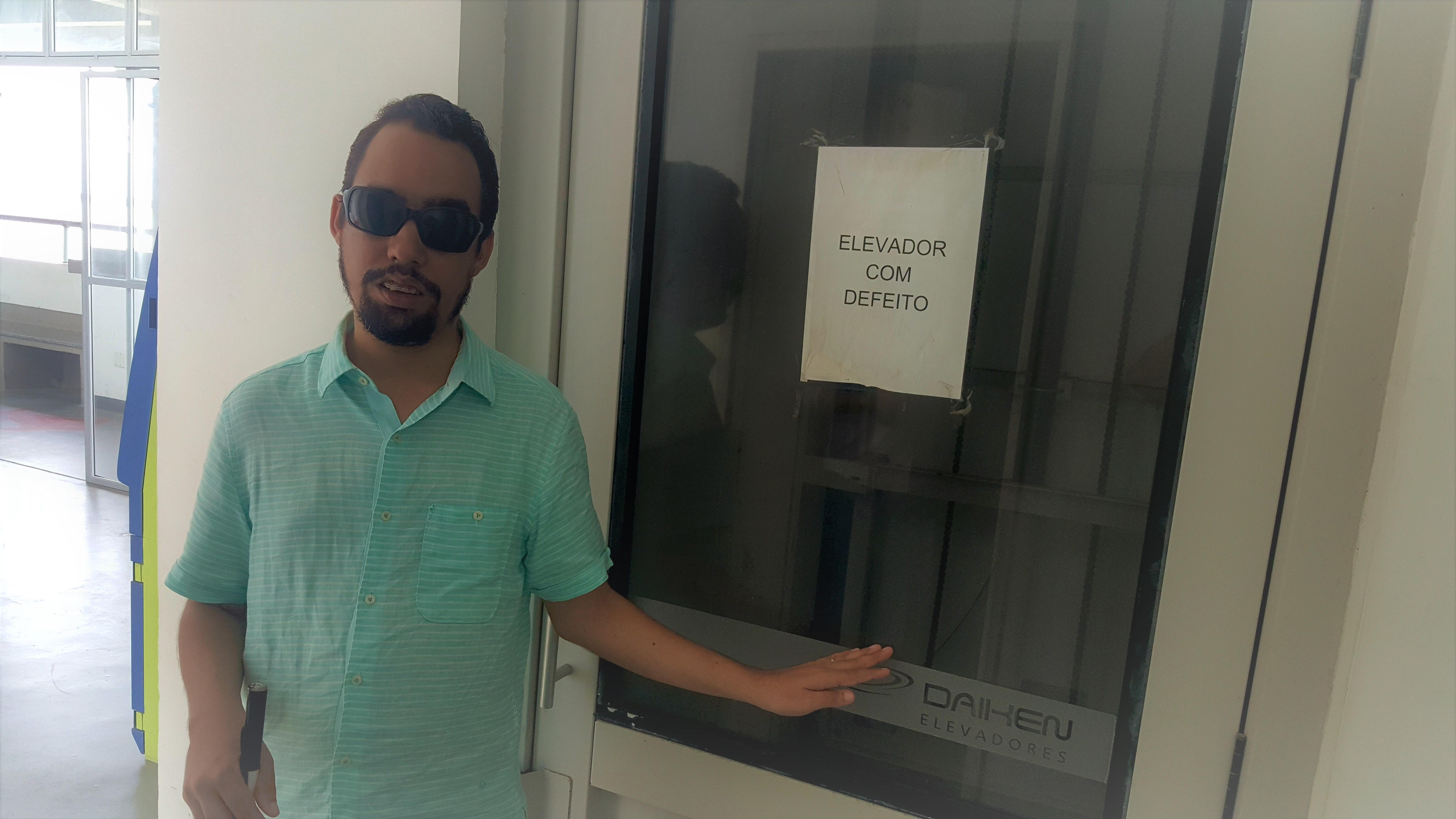 O vereador Lucas esté de pé mostrando o elevador com defeito