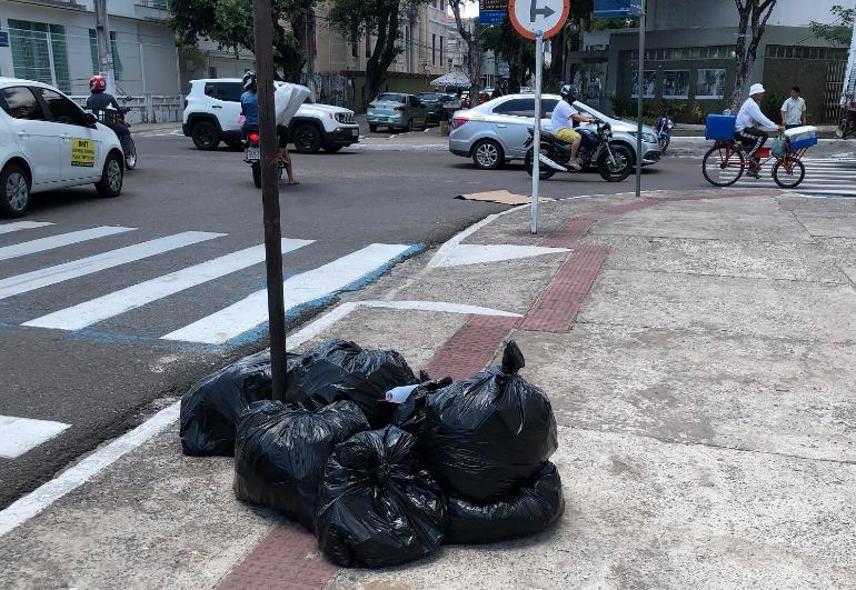 Rua, esquina e calçada com sacos de lixo sob piso tátil