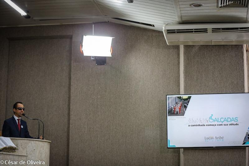 #PraTodoMundoVer Lucas Aribé está na tribuna da Câmara e ao lado tela exibe marca da campanha