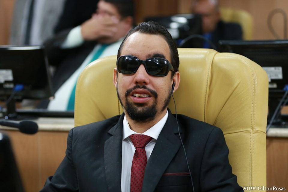 #PraTodoMundoVer Lucas Aribé sentado no plenário da Câmara Municipal de Aracaju, usando terno preto e gravata vermelha