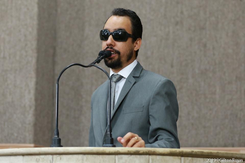 #PraTodoMundoVer Lucas Aribé falando na tribuna da Câmara, usando terno cinza