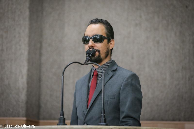 #PraTodoMundoVer Lucas Aribé discursando na tribuna da Câmara, usando terno cinza e gravata vermelha