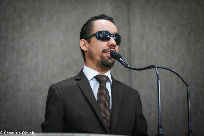 #PraTodoMundoVer Lucas Aribé discursando na tribuna, usando terno e gravata marrom