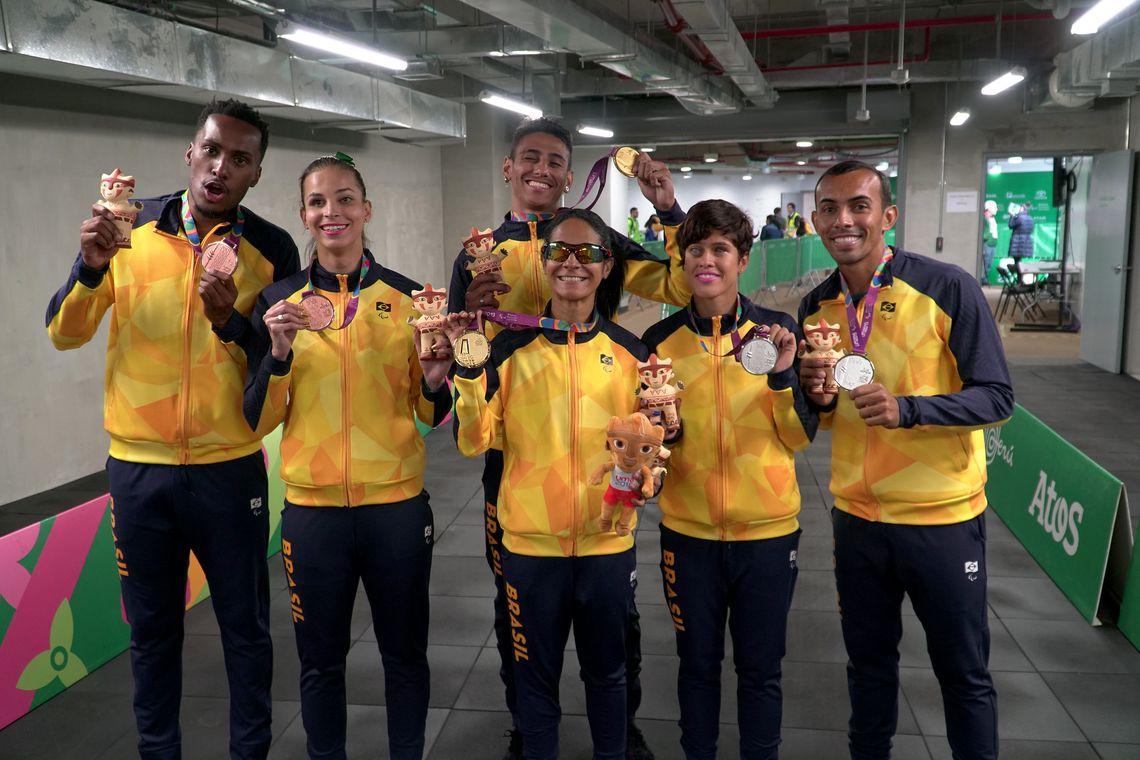 #PraTodoMundoVer Seis paratletas em pé, sorrindo para a câmera segurando suas medalhas. Foto:Rodolfo Vilela/ rededoesporte.gov.br