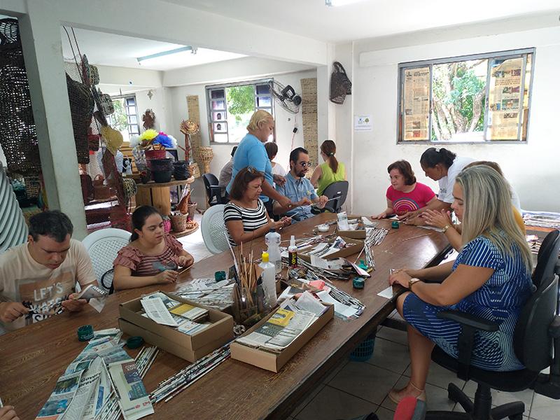 #PraTodoMundoVer Cinco pessoas sentadas junto a Lucas Aribé, todos em torno de uma mesa, onde estão os jornais e materiais para a oficina. Em pé, duas instrutoras da oficina