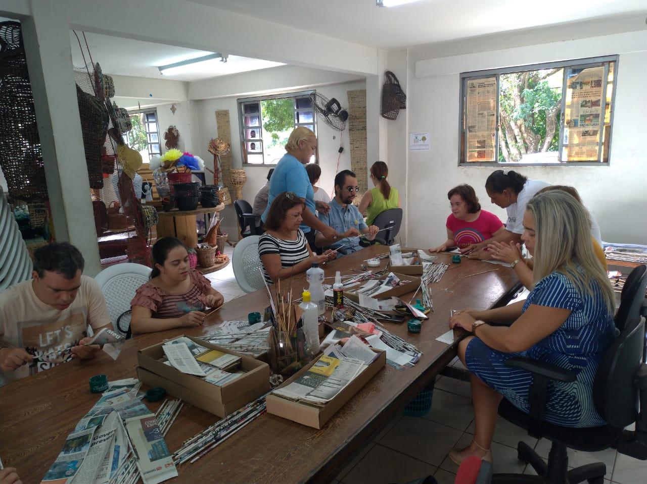#PraTodoMundoVer  Pessoas sentadas ao redor de uma mesa cheia de objetos como cola, papel, aprendem a criar objetos com papel reciclado