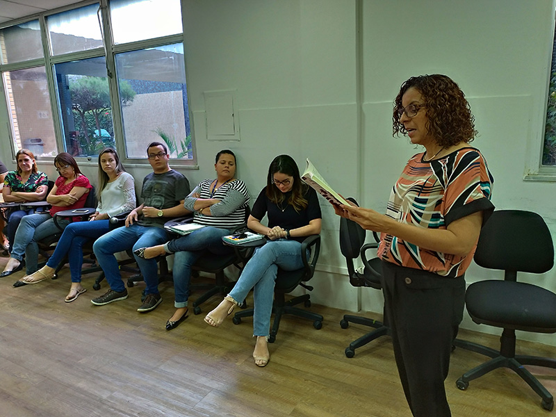 #PraTodoMundoVer Rita de Cássia está em pé à direita lendo um livro e seis pessoas estão à esquerda