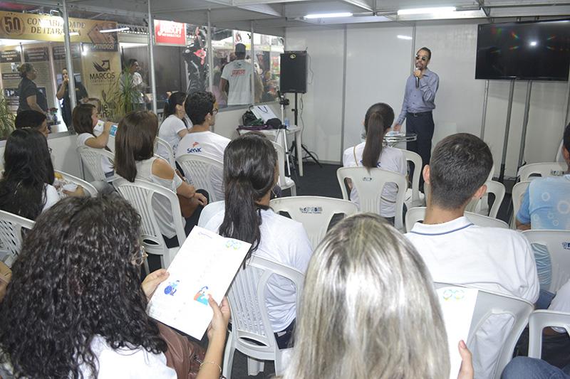 #PraTodoMundoVer Sala com pessoas sentadas em cadeiras, olhando para Lucas Aribé, que está no fundo falando ao microfone