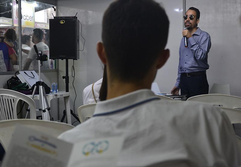 #PraTodoMundoVer Em primeiro plano, imagem de um participante de costas, e, fora de foco, uma cartilha. Ao fundo, Lucas está falando ao microfone