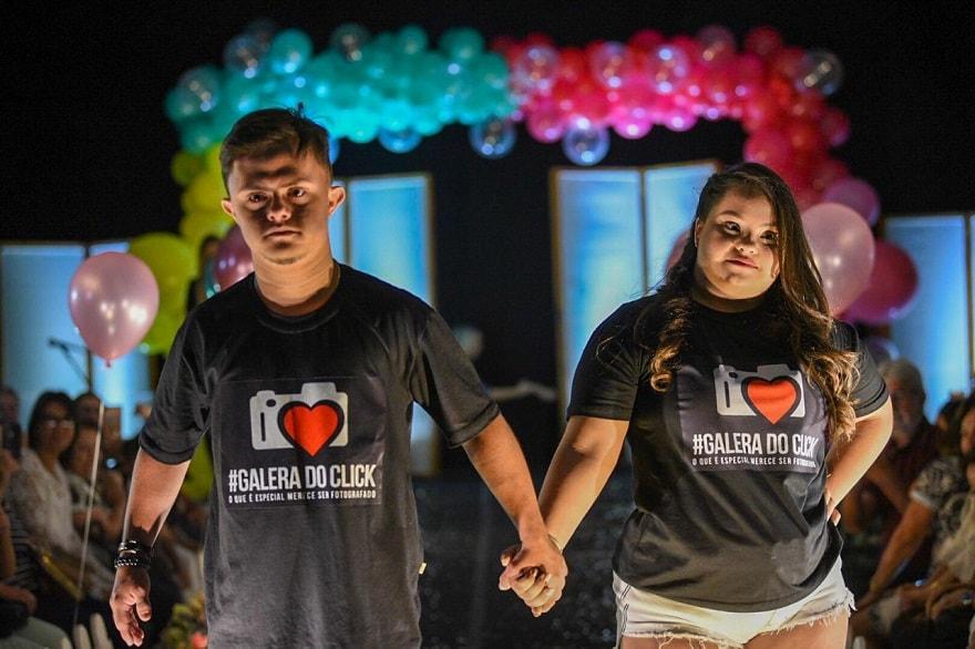 #PraTodoMundoVer Imagem horizontal de um homem e uma mulher desfilando em passarela