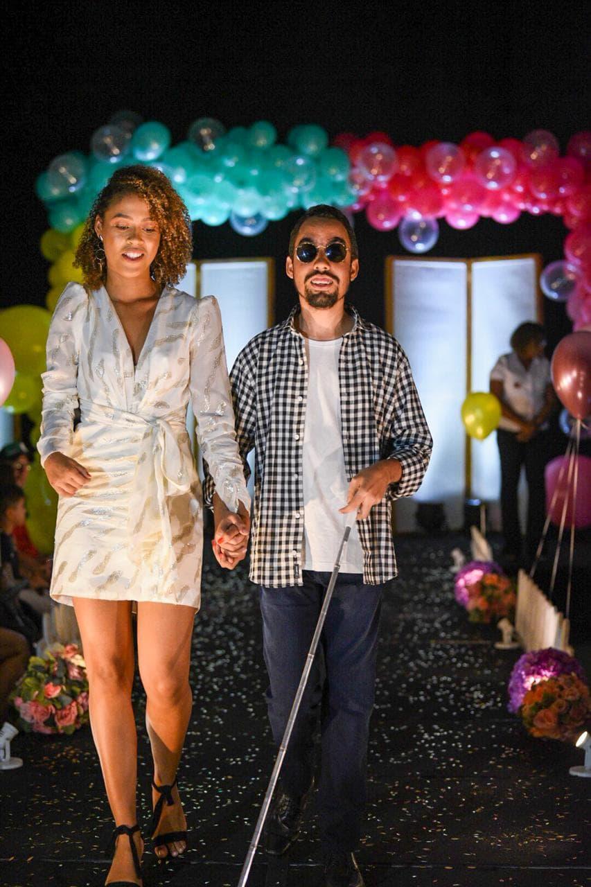 #PraTodoMundoVer Imagem vertical de um homem e uma mulher desfilando em passarela