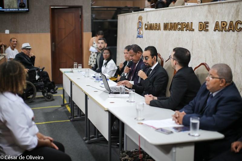 #PraTodoMundoVer Foto no plenário da CMA com pessoas ocupando mesa no piso térreo, sendo uma mulher e seis homens. À frente da mesa estão um homem sentado, um homem usuário de cadeira de rodas e uma m
