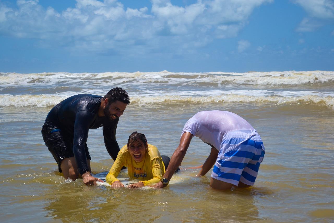 #PraTodoMundoVer Dois homens auxiliam um menino, que está na prancha de bodyboard. A mulher sorri para o registro. Eles estão no mar.