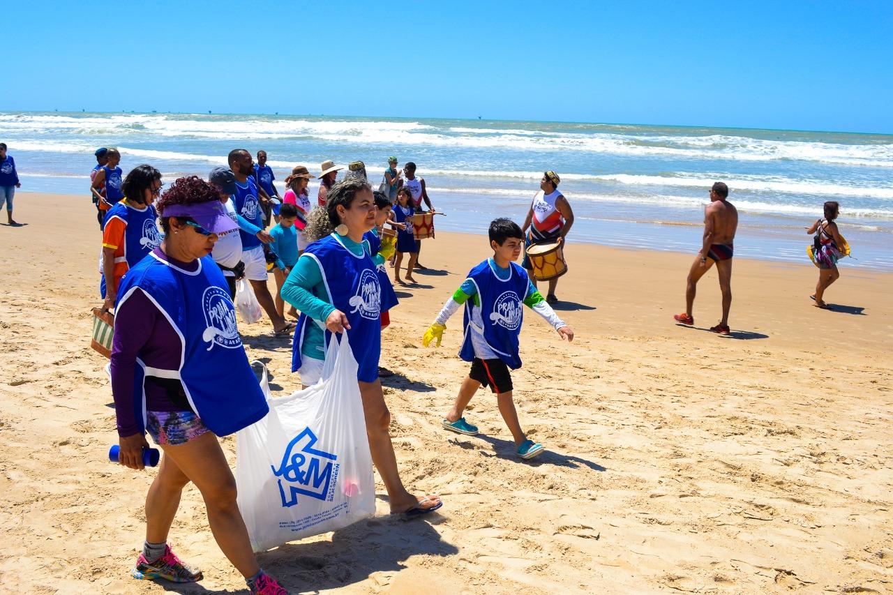 #PraTodoMundo Ver Na areia da praia, com o mar ao fundo, duas mulheres caminham segurando uma garnde sacola branca. Criança caminha ao lado.