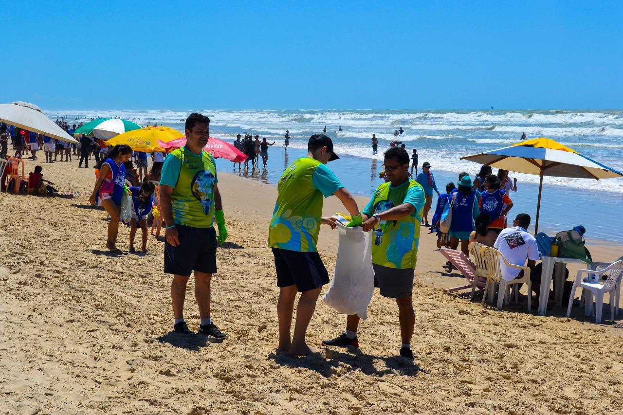 #PraTodoMundoVer Três homens estão em pé. Um deles segura um saco para recolher resíduos na praia, outro coloca lixo e o terceri o observa. Eles usam camisa verde do Colégio Amadeus