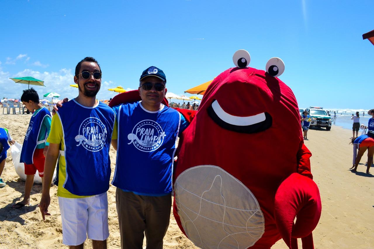 #PraTodoMundoVer Lucas e Alan, em pé, estão um ao lado do outro abraçando mascote em formato de um grande caranguejo vermelho