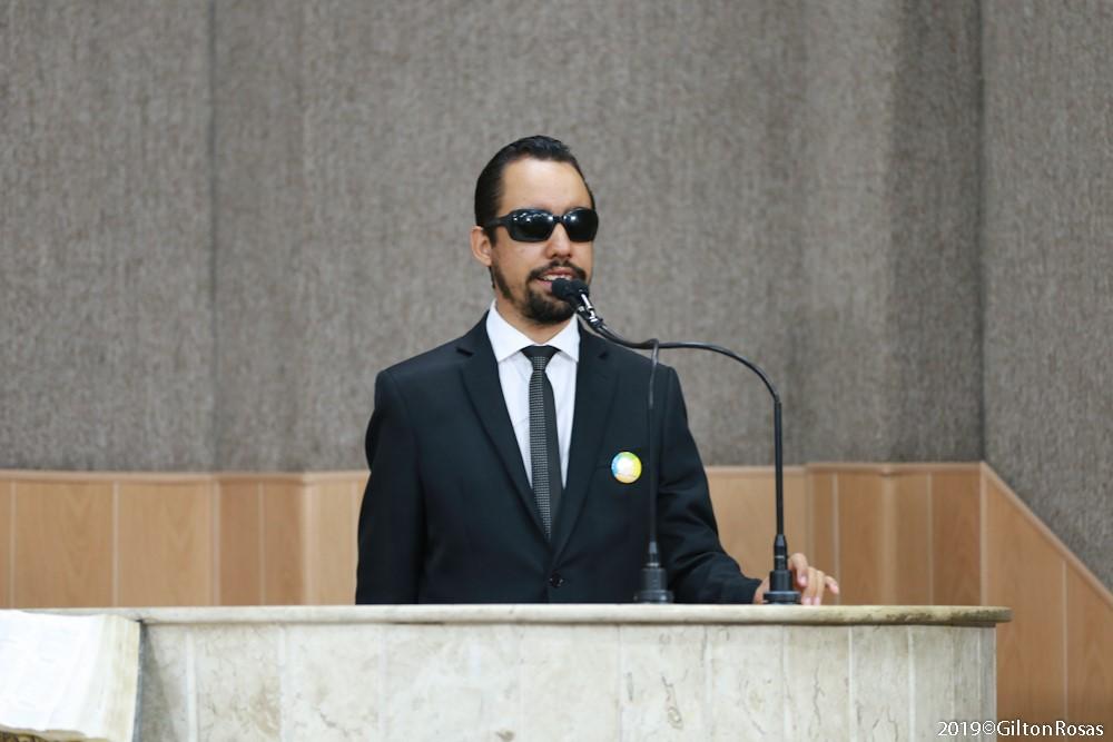 #PraTodoMundoVer Fotografia de Lucas Aribé falando ao microfone na tribuna da Câmara