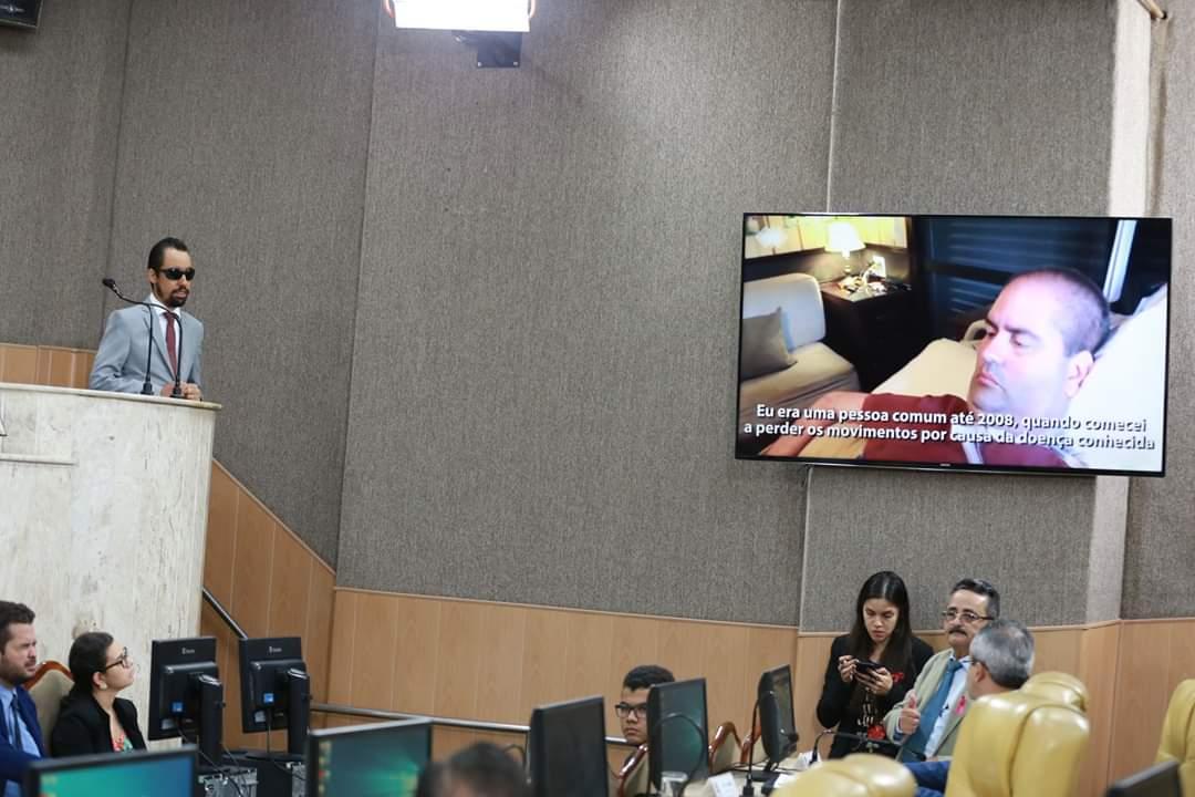 #PraTodoMundoVer Foto do plenário da CMA. À esquerda, Lucas Aribé está na tribuna e à direita, telão exibe vídeo de um homem