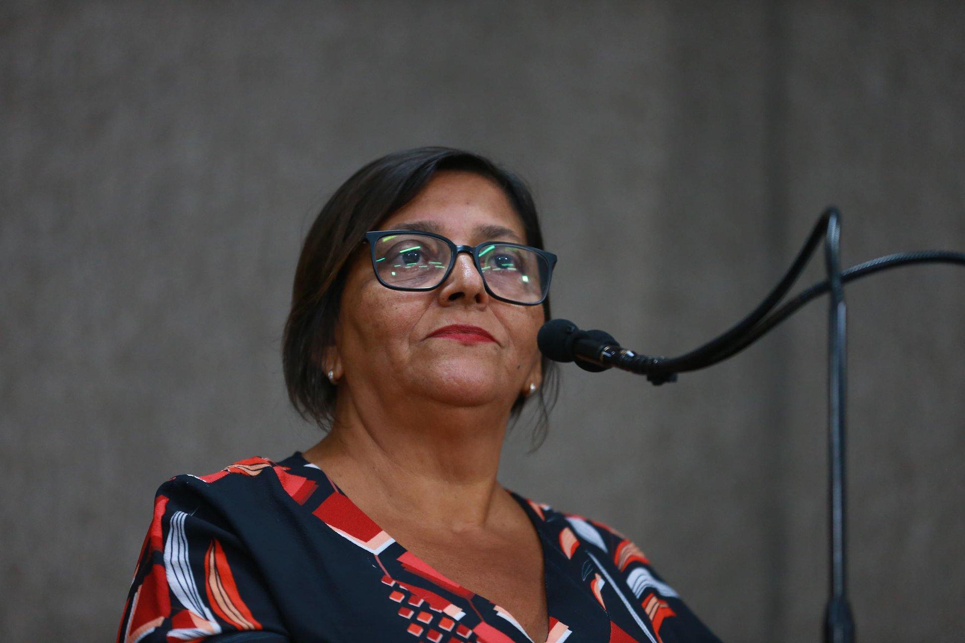 #PraTodoMundoVer Professora Margarida falando ao microfone na tribuna. Ela tem cabelos pretos curtos, usa óculos e roupa preta com estampa vermelha. (Foto: César de Oliveira)
