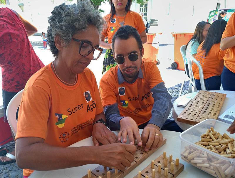 #PraTodoMundoVer Lucas sentado ao lado de uma mulher. Eles estão manuseando equipamento para o ensino do Braille.