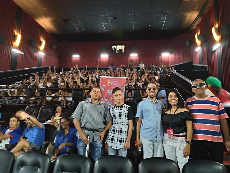 #PraTodoMundoVer Foto em uma sala de cinema. Cinco pessoas em pé à frente das cadeiras, quatro homens e uma mulher. Ao fundo, pessoas sentadas nas cadeiras do cinema estão com os braços levantados.