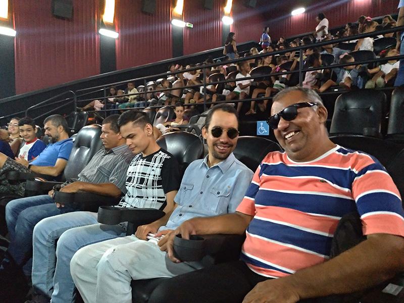 #PraTodoMundoVer Na sala de cinema, Lucas está sentado ao lado de quatro homens, sorrindo para o registro.