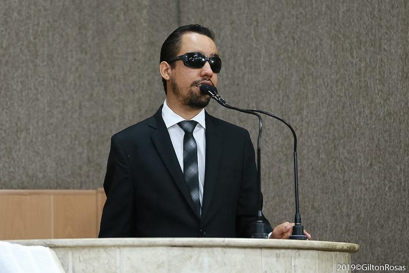 #PraTodoMundoVer Lucas Aribé em pé falando ao microfone na tribuna. Ele usa terno e gravata pretos.