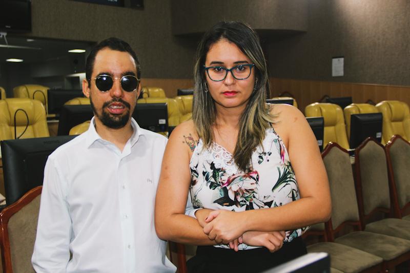 #PraTodoMundoVer Foto de Lucas Aribé e Kitty Lima em pé no plenário da CMA. Eles olham para o registro