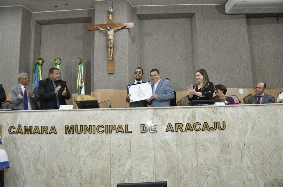 #PraTodoMundoVer Foto da mesa diretora da CMA com Lucas e o padre Rogério segurando o diploma do título. Ao lado deles, pessoas batem palmas.