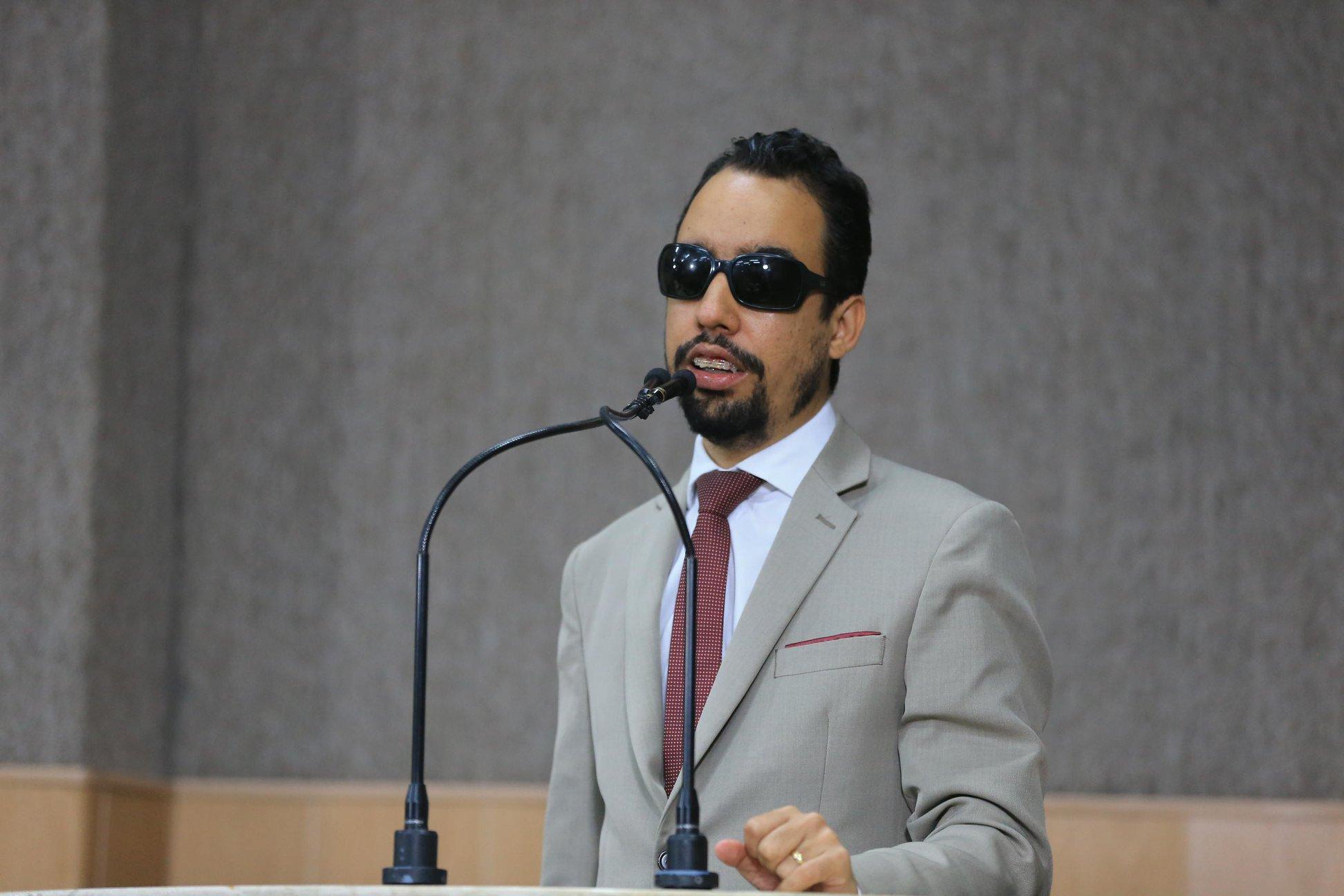 #PraTodoMundoVer Lucas Aribé está em pé na tribuna falando ao microfone. Ele usa terno cinza, camisa branca e gravata vermelha. (Foto: César Oliveira)
