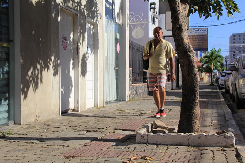 #PraTodoMundoVer Homem caminhando em calçada. À frente dele, parte da calçada está quebrada. À direita, há o tronco de uma árvore.