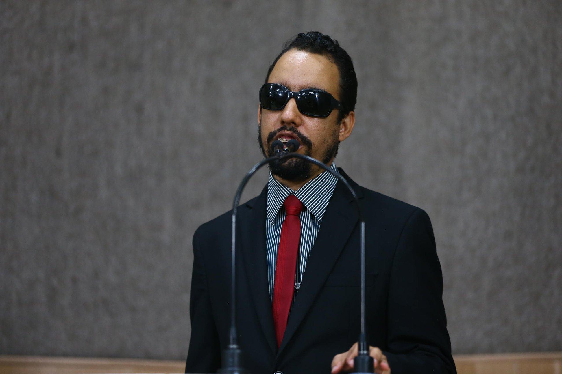 #PraTodoMundoVer Lucas em pé na tribuna falando ao microfone. Ele usa terno preto, camisa listrada em branco e preto, e gravata vermelha