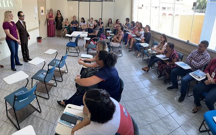 #PraTodoMundoVer Sala de aula com cadeiras,algumas ocupadas por pessoas.À esquerda,um homem e uma mulher em pé de frente para alunos.No canto superior esquerdo,duas mulheres em pé encostadas na parede