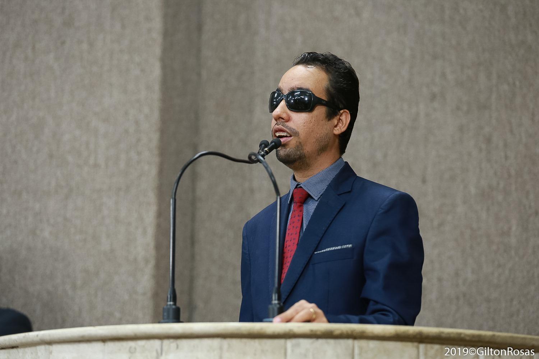 #PraTodoMundoVer Lucas Aribé em pé na tribuna da Câmara falando ao microfone. Ele usa terno e camisa azuis e gravata vermelha.