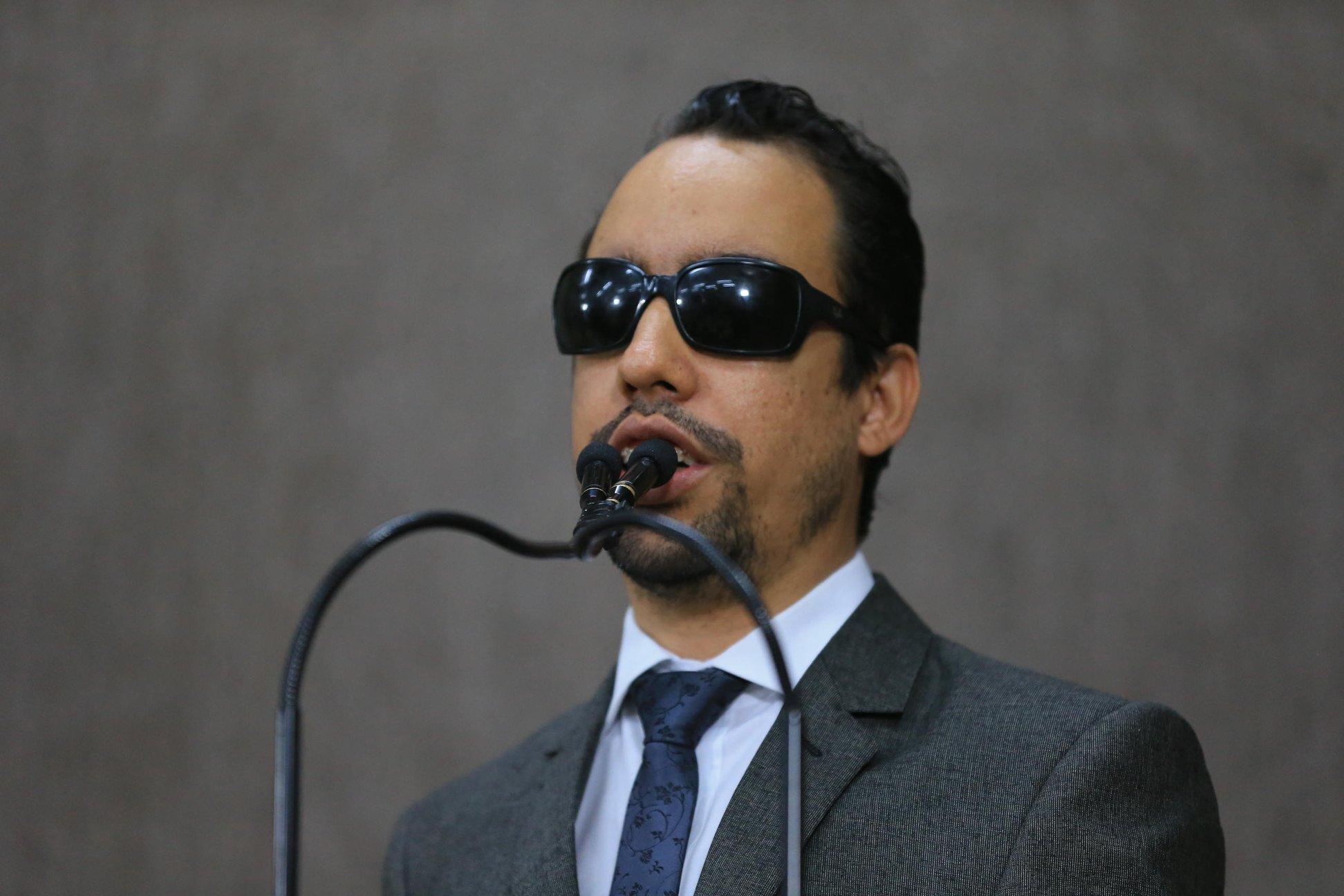 #PraTodoMundoVer Lucas Aribé em pé falando ao microfone na tribuna, Ele usa terno cinza, camisa branca e azul.