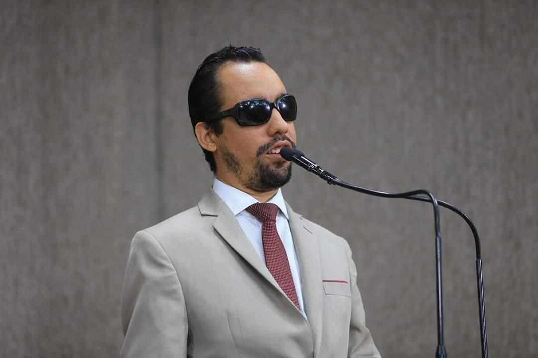 #PraTodoMundoVer Foto de Lucas falando ao microfone na tribuna da Câmara