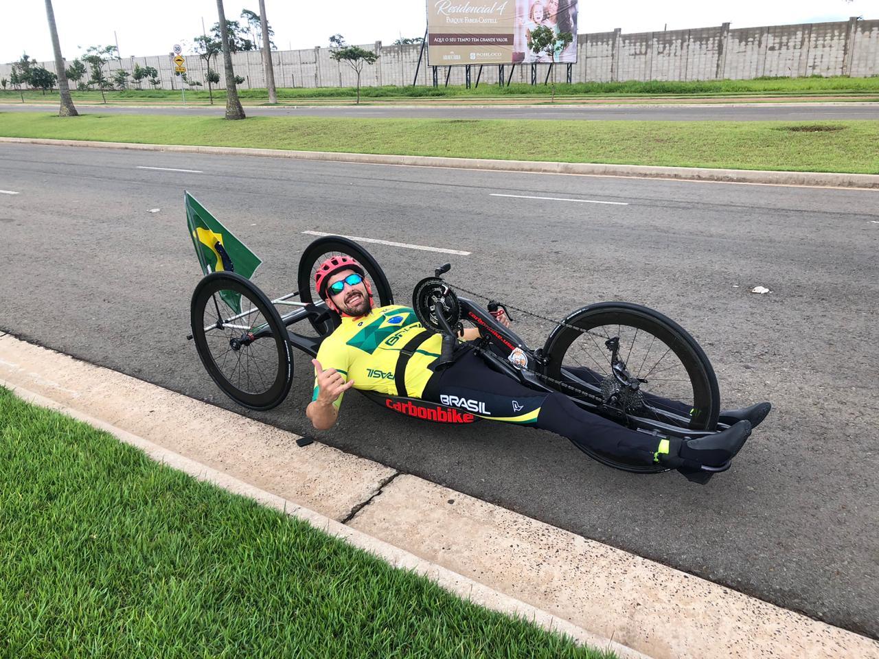 #PraTodoMundoVer Rayr Barreto em bicicleta de paraciclismo. Ele está no asfalto e, ao fundo, há um canteiro e um muro.