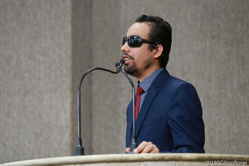 #PraTodoMundoVer Lucas está em pé falando ao microfone na tribuna. Ele usa terno preto, camisa com listras brancas e azuis e gravata vermelha.