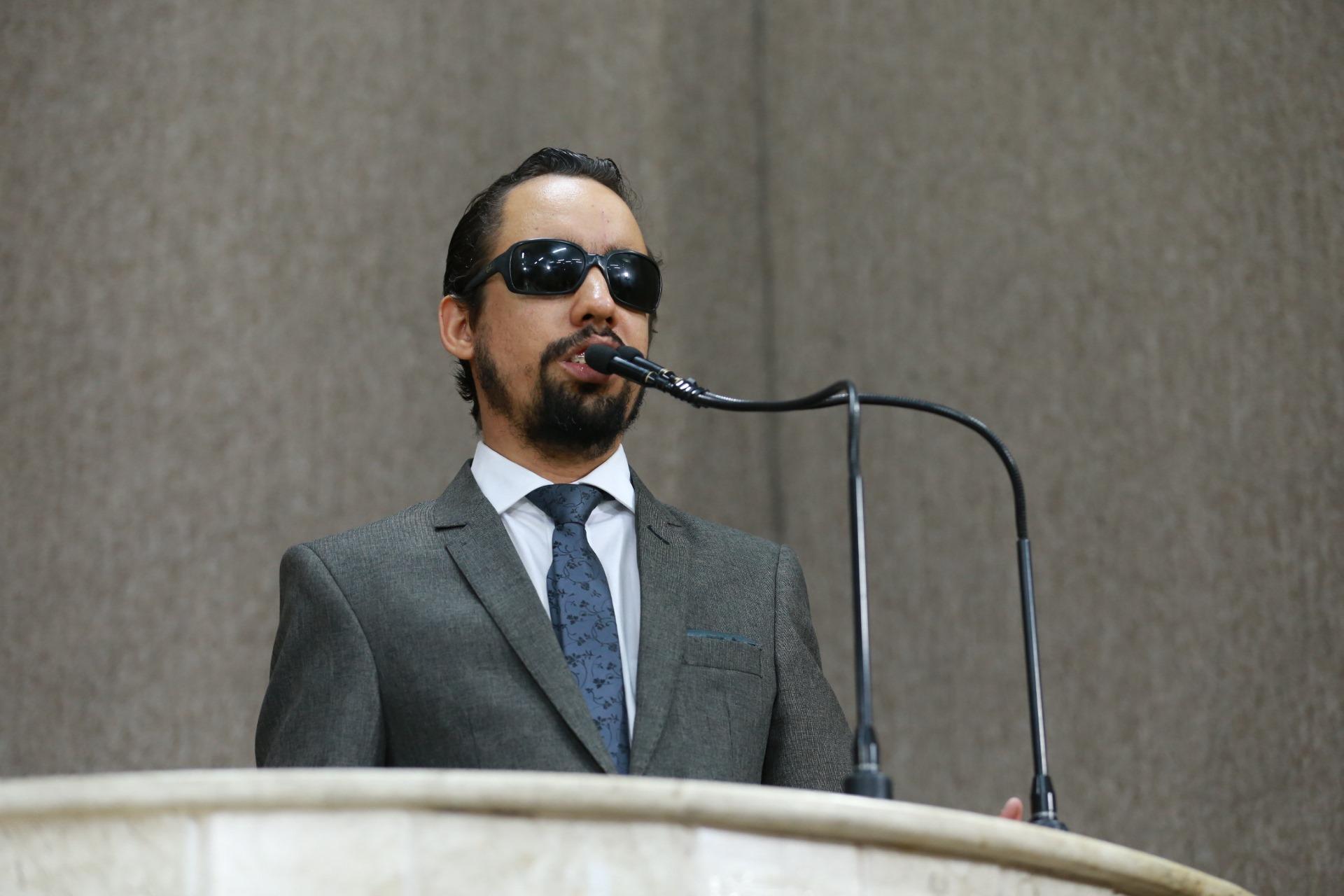 #PraTodoMundoVer Lucas em pé falando ao microfone na tribuna. Ele usa terno cinza, camisa branca e gravata cinza