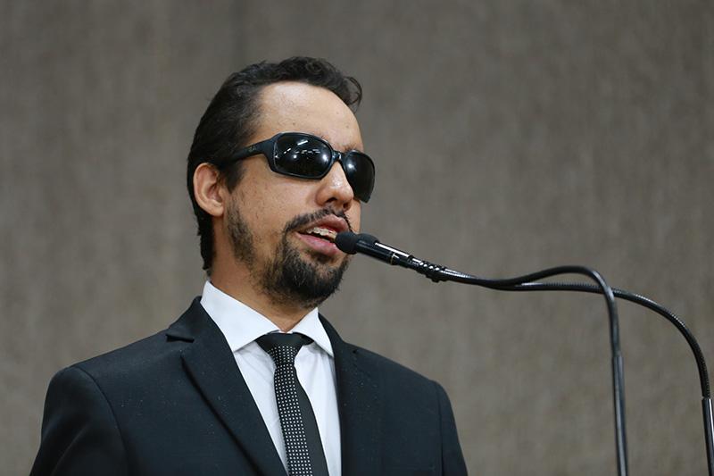 #PraTodoMundoVer Fotografia de Lucas falando ao microfone na tribuna. Ele usa óculos e terno preto.